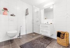 Illustrasjonsfoto av fliser, dusj, vegg-hengt toalett og servantinnredning som leveres i boligene.