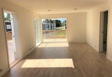 Lys og åpen stue og kjøkken med god plass til spisebord.
