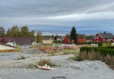 Bilde av utsikt fra tomten. Fotograf står oppå støttemur i bakkant på tomta.