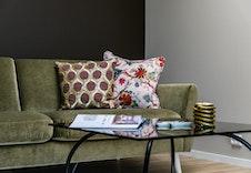 Den ene veggen i stue er malt med stilig kontrastfarge