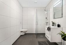 Romslig bad med dusjhjørne, vegghengt toalett, vask i seksjon og flott speil med lys.