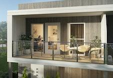 Overbygd balkong med glassrekkverk i 2. etasje til rekkehusene.