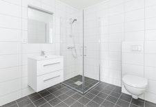 Illustrasjonsfoto av bad med samme fliser, innredning, dusj og toalett som leveres i boligene.