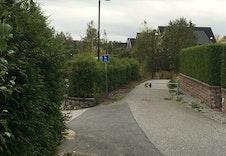 Sør for tomten hvor Romundsveien går over i gangveien som fører til skole og barnehage